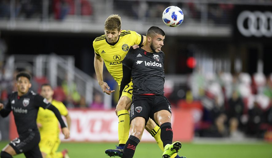 D.C. United midfielder Ulises Segura, front, battles for the ball against Columbus Crew SC defender Gaston Sauro (22) during the first half of an MLS playoff soccer match, Thursday, Nov. 1, 2018, in Washington. (AP Photo/Nick Wass) ** FILE **
