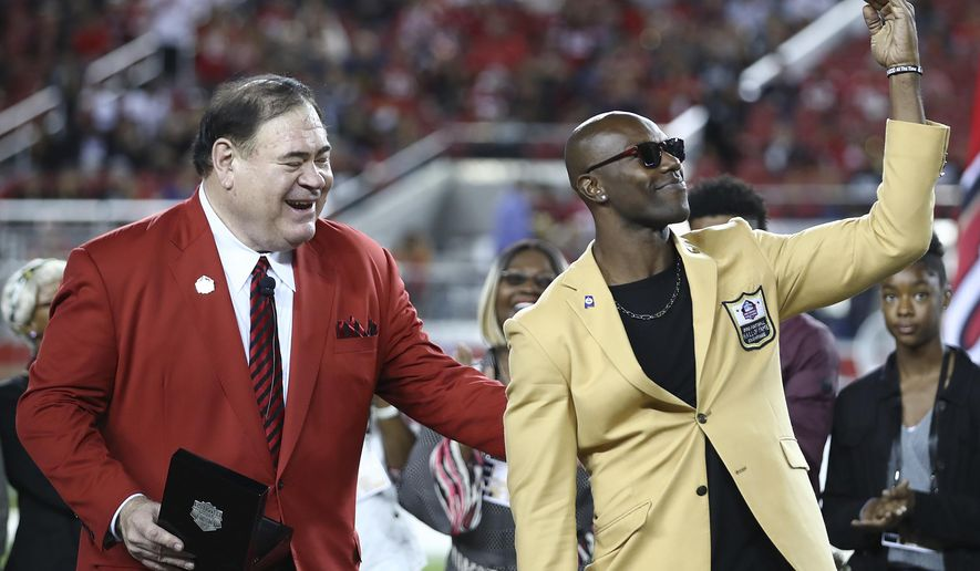 Former NFL wide receiver Terrell Owens, right, holds up his Hall of Fame ring presented by Pro Football Hall of Fame President David Baker, left, during halftime of an NFL football game between the San Francisco 49ers and the Oakland Raiders in Santa Clara, Calif., Thursday, Nov. 1, 2018. (AP Photo/Ben Margot)