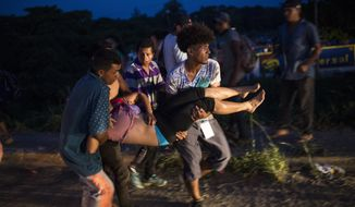 Migrants carry a friend to an ambulance after suffering a heat stroke, at an abandoned hotel in Matias Romero, Oaxaca state, Mexico, Thursday, Nov. 1, 2018. Thousands of migrants arrived in the town of Matias Romero after an exhausting 40-mile (65-kilometer) trek from Juchitan, Oaxaca, where they failed to get the bus transportation they had hoped for. (AP Photo/Rodrigo Abd)