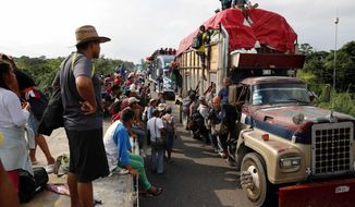 Central American migrants, part of the caravan hoping to reach the U.S. border, get a ride on trucks, in Donaji, Oaxaca state, Mexico, Friday, Nov. 2, 2018. The migrants had already made a grueling 40-mile (65-kilometer) trek from Juchitan, Oaxaca, on Thursday, after they failed to get the bus transportation they had hoped for. But hitching rides allowed them to get to Donaji early, and some headed on to a town even further north, Sayula. (AP Photo/Marco Ugarte)