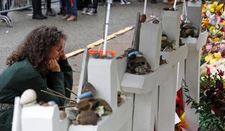Anat Halevy Hochberg, of Brooklyn, N.Y., visits a makeshift memorial outside the Tree of Life synagogue where 11 people were killed on Oct. 27 while worshipping, in the Squirrel Hill neighborhood of Pittsburgh, Thursday, Nov. 1, 2018. (AP Photo/Gene J. Puskar)