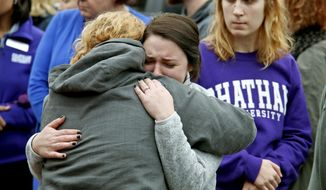 Chatham University students hug during a visit Thursday, Nov. 1, 2018, to a makeshift memorial outside the Tree of Life synagogue dedicated to the 11 people killed Oct. 27 while worshipping, in the Squirrel Hill neighborhood of Pittsburgh. (AP Photo/Gene J. Puskar)