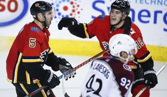 Calgary Flames defenseman Mark Giordano (5) celebrates his goal with teammate Matthew Tkachuk during the third period of an NHL hockey game against the Colorado Avalanche on Thursday, Nov. 1, 2018, in Calgary, Alberta. (Jeff McIntosh/The Canadian Press via AP)