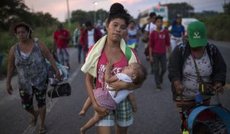 Maria Gomez, 22, carries her son David Moises, 1, as the thousands-strong caravan of Central Americans migrants hoping to reach the U.S. border moves onward from Juchitan, Oaxaca state, Mexico, Thursday, Nov. 1, 2018. Thousands of migrants resumed their slow trek through southern Mexico on Thursday, after attempts to obtain bus transport to Mexico City failed. (AP Photo/Rodrigo Abd)