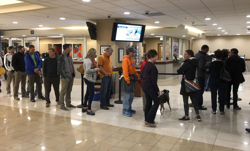 Voters wait in line at Boise City Hall in Boise, Idaho, to cast ballots in early voting Friday, Nov. 2, 2018. An unusually high number of Idahoans have voted early, and two high-profile ballot initiatives appear to be driving some of the turnout. (AP Photo/Keith Ridler)