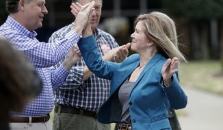 U.S. Rep. Marsha Blackburn, right, the Republican nominee for Senate, is greeted by State Sen. Jack Johnson, R-Franklin, left, as Blackburn arrives to vote Wednesday, Oct. 31, 2018, in Franklin, Tenn. (AP Photo/Mark Humphrey)
