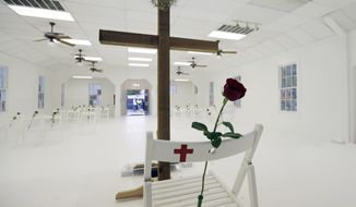 FILE - In this Nov. 12, 2017, file photo, a memorial for the victims of the shooting at Sutherland Springs First Baptist Church is shown and includes 26 white chairs, each painted with a cross and and rose, and is displayed in the church in Sutherland Springs, Texas. The anniversary of the deadliest church shooting in the nation's history _ when a gunman killed 25 people in the rural church near San Antonio _ is the day before the Texas Senate election between Republican incumbent Ted Cruz and rising Democratic star Beto O'Rourke. But you wouldn't know it spending time with either campaign. That massacre in Sutherland Springs, and another Texas mass shooting at Santa Fe High School near Houston about six months later, aren't the race's top issues. (AP Photo/Eric Gay, File)