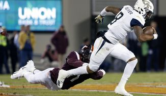 FILE - In this Oct. 25, 2018, file photo, Georgia Tech quarterback Tobias Oliver (8) tries to break the tackle of Virginia Tech defensive lineman Houshun Gaines (11) during the first half of an NCAA college football game, in Blacksburg, Va. TaQuon Marshall is keeping his starting job as Georgia Tech's quarterback after Tobias Oliver posted huge numbers as a runner in last week's upset win at Virginia Tech. Marshall won't have the position to himself. Coach Paul Johnson says he plans to play both quarterbacks in Saturday's game at North Carolina. (AP Photo/Steve Helber, File)