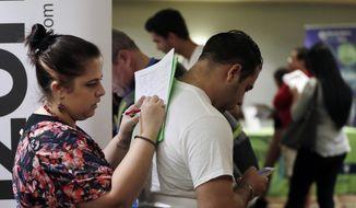 In this Jan. 30, 2018, file photo, Loredana Gonzalez, of Doral, Fla., fills out a job application at a JobNewsUSA job fair in Miami Lakes, Fla. (AP Photo/Lynne Sladky, File)