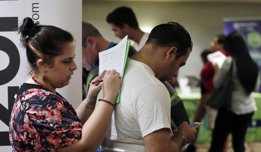 In this Jan. 30, 2018, file photo, Loredana Gonzalez, of Doral, Fla., fills out a job application at a JobNewsUSA job fair in Miami Lakes, Fla. (AP Photo/Lynne Sladky, File)