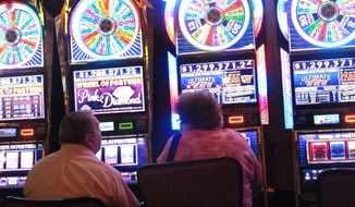 This June 24, 2016 photo shows gamblers playing slot machines at the Golden Nugget casino in Atlantic City N.J. The casino is seeking an internet gambling license in Pennsylvania, part of a growing crossover between casinos in the neighboring states to compete in each other's online and sports betting markets. (AP Photo/Wayne Parry)