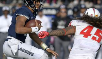 Utah State quarterback Jordan Love (10) carries the ball as New Mexico linebacker Evahelotu Tohi (45) defends during an NCAA college football game, Saturday, Oct. 27, 2018, in Logan, Utah. (Eli Lucero/The Herald Journal via AP)