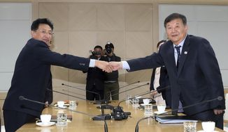 Roh Tae-kang, right, South Korea's vice minister of culture and sports, shakes hands with his North Korean counterpart Won Kil U while posing for a photo during a meeting at the inter-Korean liaison office in Kaesong, North Korea, Friday, Nov. 2, 2018. North and South Korea agreed to officially inform the International Olympic Committee of their intent to co-host the 2032 Summer Olympics. (Korea Pool/Yonhap via AP)