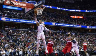 Oklahoma City Thunder guard Russell Westbrook (0) goes for a layup past Washington Wizards guard John Wall (2) and forward Markieff Morris (5) during the first half of an NBA basketball game Friday, Nov. 2, 2018, in Washington. (AP Photo/Al Drago) **FILE**