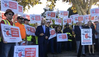 Protestors gather at a rally and hold signs on behalf of a campaign against Proposition 6 during a visit and support by Gov. Jerry Brown on Friday Nov. 2, 2018 in Palo Alto, Calif. Proposition 6, which would repeal an increase in gas tax and vehicle fees for transportation projects in California. (AP Photo/Janie Har)