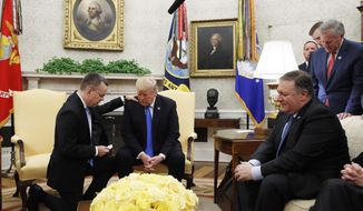 In this Oct. 13, 2018, file photo President Donald Trump prays with American pastor Andrew Brunson in the Oval Office of the White House in Washington. Brunson had returned to the U.S. after he was freed from nearly two years of detention in Turkey.  The United States has lifted sanctions on two senior Turkish officials that were imposed in connection with the detention of American pastor Andrew Brunson. (AP Photo/Jacquelyn Martin)