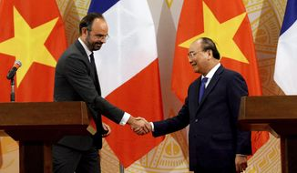 French Primer Minister Edouard Philippe, left, shakes hands with Vietnam's Prime Minister Nguyen Xuan Phuc speaks during their joint press conference at International Convention Center in Hanoi, Friday, Nov. 2, 2018. (Nhac Nguyen/Pool Photo via AP)
