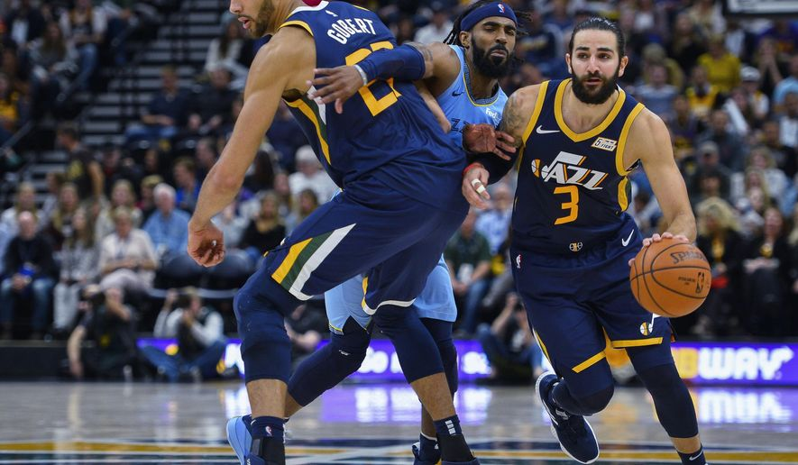 Utah Jazz guard Ricky Rubio (3) drives around teammate Rudy Gobert (27) and Memphis Grizzlies guard Mike Conley (11) during the second half of an NBA basketball game Friday, Nov. 2, 2018, in Salt Lake City. (AP Photo/Alex Goodlett)