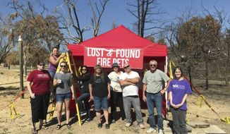 """In this undated photo, Volunteers with Carr Fire Pet Rescue and Reunification pose with their """"Lost and Found Fire Pets"""" kiosk in Redding, Calif. Volunteers continue to track and catch missing pets nearly two months after the fire was extinguished. They post pictures of the rescued pets in hopes that their owners will recognize them and reunite with them. More than 80 families who lost their homes in California's deadly Carr Fire in July have learned weeks or months later that their dogs and cats had survived the deadly disaster. (Courtesy of Stacey Jimenez via AP)"""