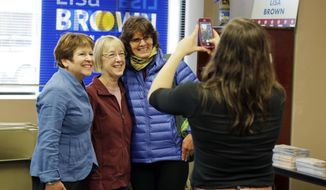 In this Oct. 28, 2018 photo, Lisa Brown, left, the Democrat challenging Rep. Cathy McMorris-Rodgers, R-Wash., for her 5th Congressional District seat, poses for a photo with a supporter, right, and U.S. Sen. Patty Murray, D-Wash., center, following a pep talk with Murray to volunteers at Brown's campaign office in Spokane, Wash. (AP Photo/Ted S. Warren)