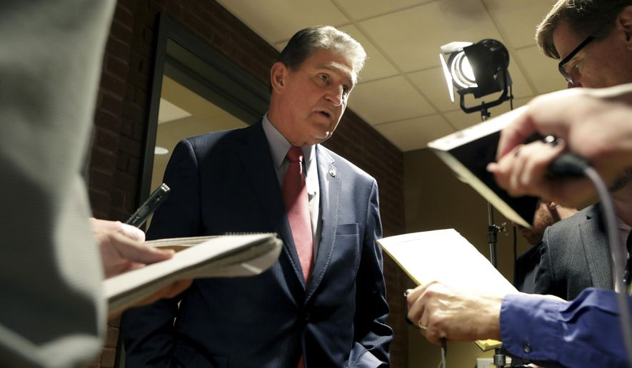 In this Nov. 1, 2018 photo, Sen. Joe Manchin speaks to reporters after a debate with Patrick Morrisey in Morgantown, W.Va. Republicans have a huge advantage as they seek to hold or expand their 51-49 Senate majority, with the battle for control running mostly through states that President Donald Trump won in 2016.   (AP Photo/Raymond Thompson)