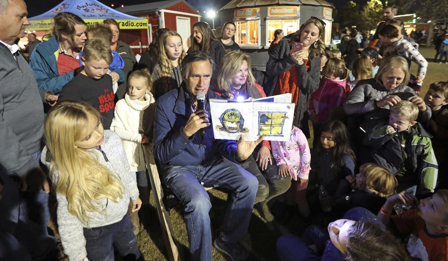 In this Friday, Nov. 2, 2018 photo, former GOP presidential nominee Mitt Romney and his wife Ann read a children's book during scary tales and smores bonfire at Cornbelly's Corn Maze & Pumpkin Fest at Thanksgiving Point in Lehi, Utah. Romney is stumping for fellow Republican candidates as he sails toward a likely victory Tuesday, Nov. 6, in the race for a U.S. Senate seat from Utah and an official return to public office. (AP Photo/Rick Bowmer)
