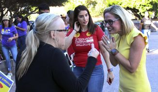 A supporter, left, crosses her fingers as she talks with Democratic U.S. Senate candidate Kyrsten Sinema, right, at a get-out-the-vote event at the Arizona Education Association headquarters in Phoenix Saturday, Nov. 3, 2018. Sinema takes on Republican Martha McSally in the race to replace Republican Sen. Jeff Flake, who is retiring.  (AP Photo/Bob Christie)