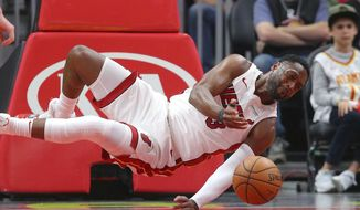 Miami Heat guard Dwyane Wade (3) dives for a loose ball during the first half of an NBA basketball game against the Atlanta Hawks Saturday, Nov. 3, 2018, in Atlanta. (AP Photo/John Bazemore)