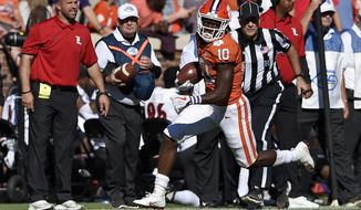 Clemson's Derion Kendrick subbing as quarterback, scrambles and runs for a first down during the second half of an NCAA college football game against Louisville, Saturday, Nov. 3, 2018, in Clemson, S.C. Clemson won 77-16. (AP Photo/Richard Shiro)