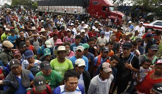 Central American migrants, part of the caravan hoping to reach the U.S. border, wait to get a ride on a truck, in Isla, Veracruz state, Mexico, Saturday, Nov. 3, 2018. (AP Photo/Marco Ugarte)
