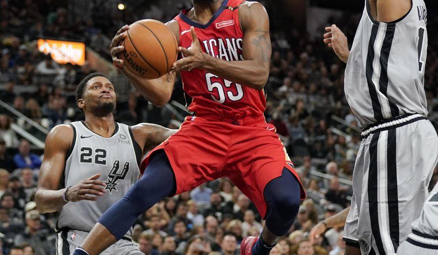 New Orleans Pelicans' E'Twaun Moore (55) looks to pass as he drives between San Antonio Spurs' LaMarcus Aldridge, right, and Rudy Gay during the first half of an NBA basketball game, Saturday, Nov. 3, 2018, in San Antonio. (AP Photo/Darren Abate)