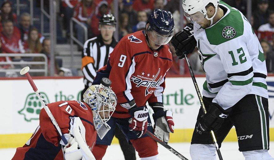 Dallas Stars center Radek Faksa (12), of the Czech Republic, fight for the puck against Washington Capitals goaltender Braden Holtby (70) and defenseman Dmitry Orlov (9), of Russia, during the first period of an NHL hockey game, Saturday, Nov. 3, 2018, in Washington. (AP Photo/Nick Wass)