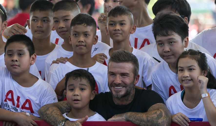 """Retired footballer David Beckham poses for a group photograph during a sponsored promotional event in Bangkok, Thailand, Saturday, Nov 3, 2018. Beckham made a brief appearance to conducted soccer drills and addressed a crowd of around a hundred young soccer fans as part of a sponsored promotional event """"AIA Football Clinic for Youth with Leading Coaches"""" that also featured coaches from Tottenham Hotspurs as well as Thai celebrities and soccer players. (AP Photo/Gemunu Amarasinghe)"""