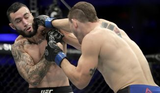 Kurt Holobaugh, right, lands a punch to Shane Burgos during the first round of a featherweight mixed martial arts bout at UFC 230, Saturday, Nov. 3, 2018, at Madison Square Garden in New York. (AP Photo/Julio Cortez)