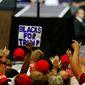 "A man raises a sign ""Blacks For Trump"" as President Trump speaks on June 27 in Fargo, North Dakota. (Associated Press)"
