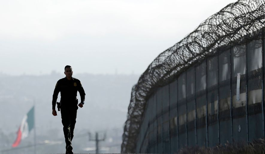 In this June 22, 2016, file photo, Border Patrol agent Eduardo Olmos walks near the secondary fence separating Tijuana, Mexico, background, and San Diego in San Diego. In his threat Tuesday, April 3, 2018, to use the military on the U.S.-Mexico border until his promised wall is built, President Donald Trump again heaped blame on his predecessor, Barack Obama, and congressional Democrats for creating a dangerous and dysfunctional border. (AP Photo/Gregory Bull, File)