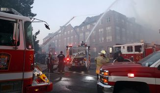 In this Sept. 19, 2018, photo, firefighters pour water on a fire at the Arthur Capper Senior Building, an apartment building that houses senior citizens. Engineers made a startling discovery while inspecting the wreck of a fire-damaged public housing complex. They found a 74-year-old tenant, alive and well, five days after the whole building was supposedly evacuated in the midst of the blaze. (AP Photo/Alex Brandon)