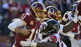 Washington Redskins quarterback Alex Smith (left) is sacked by Atlanta Falcons defensive tackle Grady Jarrett (right) during an NFL football game between the Atlanta Falcons and Washington Redskins, Sunday, Nov. 4, 2018, in Landover, Md. (AP Photo/Mark Tenally) **FILE**