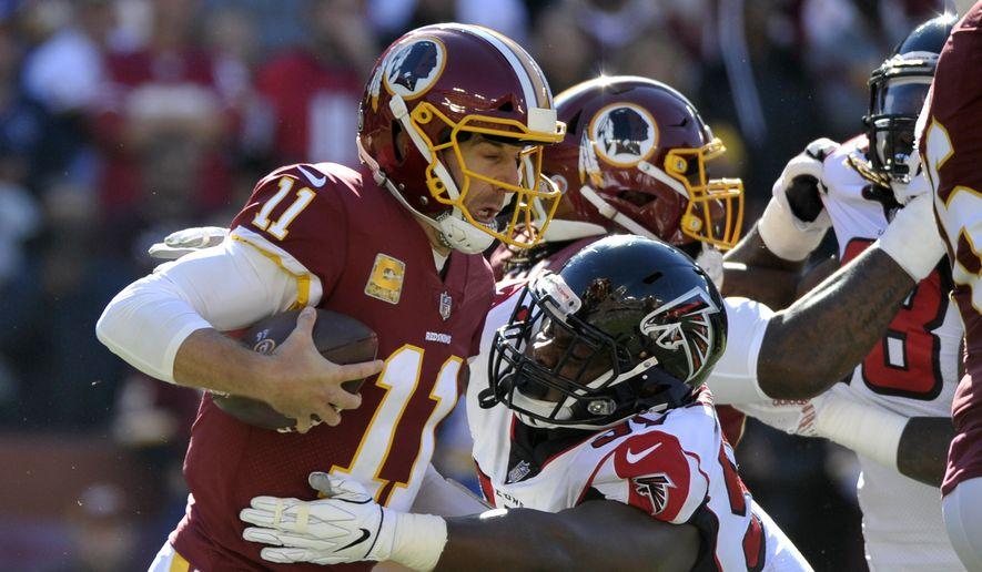 Washington Redskins quarterback Alex Smith (left) is sacked by Atlanta Falcons defensive tackle Grady Jarrett (right) during an NFL football game between the Atlanta Falcons and Washington Redskins, Sunday, Nov. 4, 2018, in Landover, Md. (AP Photo/Mark Tenally) **FILE**