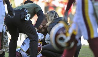 Trainers help Washington Redskins offensive guard Brandon Scherff (75) after an injury during the second half of an NFL football game between the Atlanta Falcons and the Washington Redskins, Sunday, Nov. 4, 2018 in Landover, Md. (AP Photo/Mark Tenally)