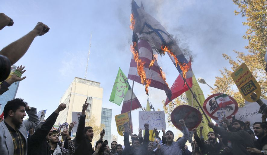 Iranian demonstrators burn representations of the U.S. and Israeli flags during a rally in front of the former U.S. Embassy in Tehran, Iran, on Sunday, Nov. 4, 2018, marking the 39th anniversary of the seizure of the embassy by militant Iranian students. Thousands of Iranians rallied in Tehran on Sunday to mark the anniversary as Washington restored all sanctions lifted under the nuclear deal. (AP Photo/Vahid Salemi)