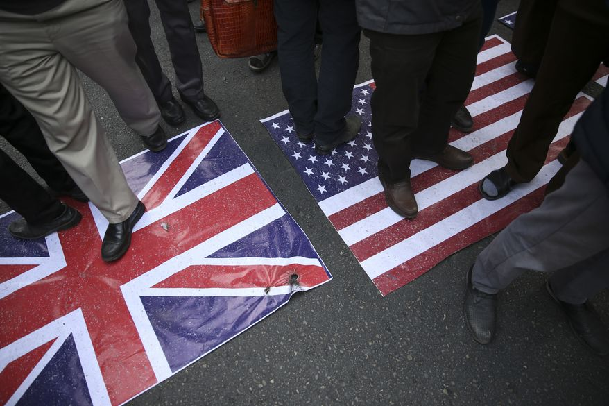 Representations of the U.S. and British flags are walked on by demonstrators during an annual rally in front of the former U.S. Embassy in Tehran, Iran, on Sunday, Nov. 4, 2018, to mark the 39th anniversary of the seizure of the embassy by militant Iranian students. Thousands of Iranians rallied in Tehran on Sunday to mark the anniversary as Washington restored all sanctions lifted under the nuclear deal. (AP Photo/Vahid Salemi)