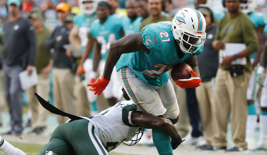 New York Jets cornerback Morris Claiborne (21) tackles Miami Dolphins running back Frank Gore (21), during the first half of an NFL football game, Sunday, Nov. 4, 2018, in Miami Gardens, Fla. (AP Photo/Wilfredo Lee)