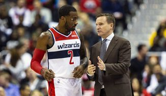 Washington Wizards head coach Scott Brooks speaks with guard John Wall (2) during the second half of an NBA basketball game against the New York Knicks, Sunday, Nov. 4, 2018, in Washington. (AP Photo/Al Drago) **FILE**