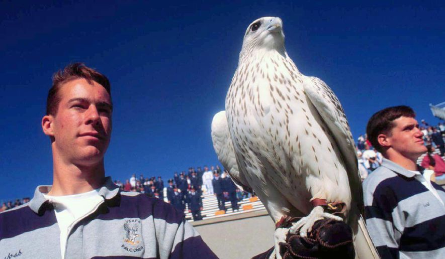 In this Sept. 28, 1996, photo Air Force Academy falconer Josh Johnson stands with falcon Aurora, the academy's official mascot, at the end of a game against Rice at Air Force Academy, Colo. Animal rights activist group PETA is urging the academy to stop using a live falcon as its mascot. (The Gazette via AP)  **FILE**