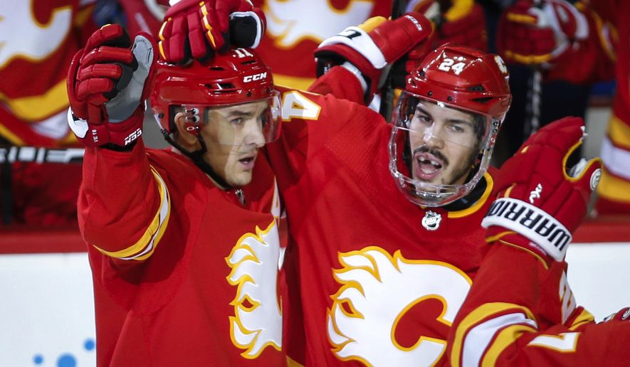 Calgary Flames' Mikael Backlund, left, of Sweden, celebrates his goal with teammate Travis Hamonic during the third period of an NHL hockey game against the Chicago Blackhawks in Calgary, Alberta, Saturday, Nov. 3, 2018. Calgary won, 5-3. (Jeff McIntosh/The Canadian Press via AP)