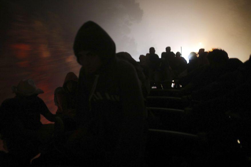 Central American migrants, part of the caravan hoping to reach the U.S. border, travel during the night on a truck in Orizaba, Veracruz state, Mexico, Saturday, Nov. 3, 2018. (AP Photo/Rodrigo Abd)