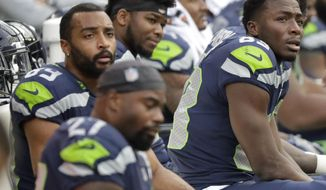 Seattle Seahawks players, including wide receivers David Moore, right, and Doug Baldwin, upper left, sit on the bench late in the second half of an NFL football game against the Los Angeles Chargers, Sunday, Nov. 4, 2018, in Seattle. (AP Photo/Ted S. Warren)