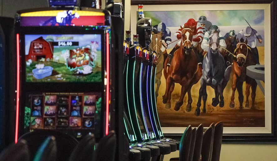 FILE - This March 5, 2015 file photo shows video gaming terminals known as instant horse racing at Les Bois Park in Garden City, Idaho. Such machines are now banned in Idaho, but a new ballot initiative, Proposition 1, has been filed to legalize the machines. (AP Photo/Otto Kitsinger, File)