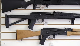 Semi-automatic rifles are displayed on a wall at a gun shop. (AP Photo/Elaine Thompson, File)